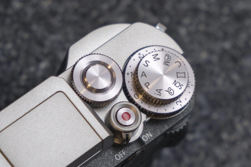 Присутствует задний диск, в то же время как диск режимов расположен над диском компенсации экспозиции напоминает слоистый пирог.